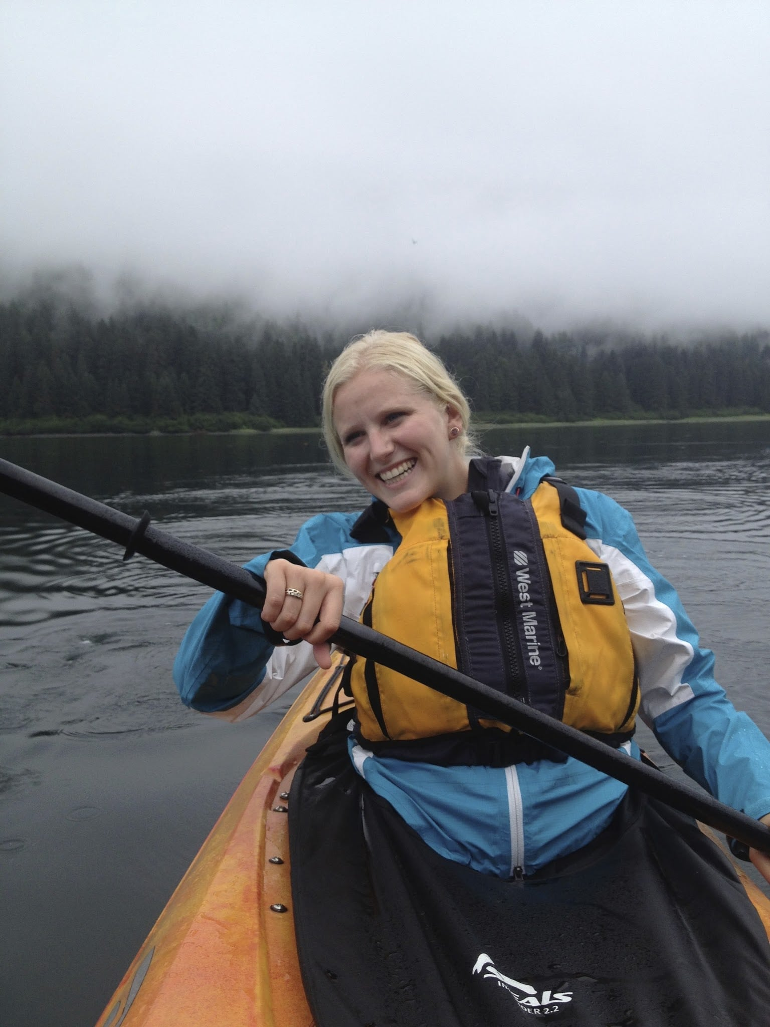 woman paddling canoe and smiling